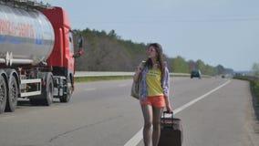 A moça com mala de viagem e trouxa anda perto da estrada video estoque