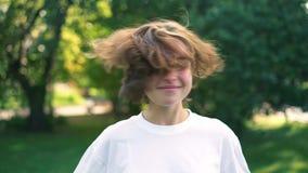 Moça com o cabelo justo curto que joga com eles no parque do verão filme