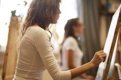 A moça com o cabelo marrom encaracolado vestido na blusa branca tira uma imagem com um lápis na escola de tiragem fotografia de stock royalty free