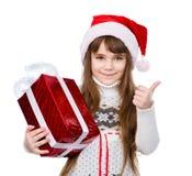 Moça com o chapéu vermelho de Santa que guarda a caixa de presente e que mostra o polegar acima Isolado no branco Imagens de Stock