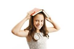 Moça com o livro sobre sua cabeça fotografia de stock