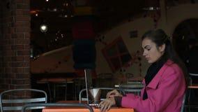 Moça com o portátil na tabela no café que fala no telefone filme