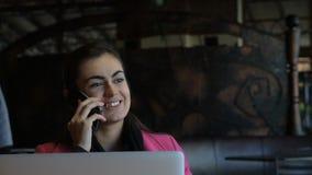 Moça com o portátil na tabela no café que fala no telefone video estoque