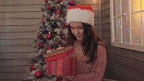 Moça com o presente aberto do chapéu do Natal Sorrisos da menina com presente do Natal à disposição video estoque