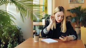 Moça com o smartphone que faz os trabalhos de casa que sentam-se no café A mulher escreve para baixo algo de seu telefone ao cade video estoque