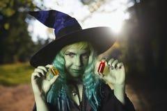 A moça com o terno verde do cabelo e da pele da bruxa na floresta guarda garrafas pequenas com poção vermelha e alaranjada Tempo  Imagem de Stock