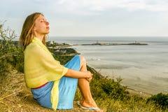 A moça com olhos fechados está sentando-se em uma costa alta acima do mar e está apreciando-se o sol da noite Imagens de Stock