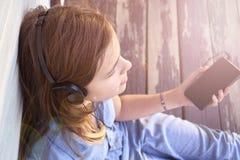 A moça com olhos fechados que aprecia a música fora com fones de ouvido e um smartphone iluminou-se por raios do sol imagem de stock royalty free