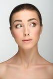 Moça com olhos grandes e as sobrancelhas escuras, ombros despidos, olhando para, uma composição clara modelo do nude, fundo cinze Foto de Stock Royalty Free