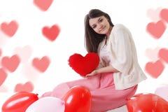 Moça com os balões vermelhos no bokeh coração-dado forma imagens de stock royalty free
