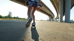 Moça com os pés delgados que montam um skate sob a ponte vídeos de arquivo
