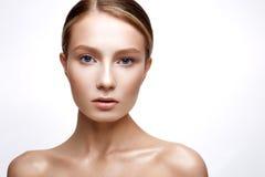 Moça com pele de brilho perfeita Um modelo bonito com uma composição da fundação e do nude Limpe a pele Fundo isolado branco imagem de stock
