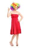 Moça com peruca que aponta acima com dedo Imagem de Stock