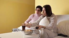 Moça com sua mamã em casa no sofá que olha a tevê e que come microplaquetas e que bebe a cola noite Casa conforto video estoque