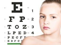 Moça com a tabela da visão do teste sobre o fundo conceito da visão do ` s das crianças da preservação Imagem de Stock Royalty Free