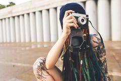 A moça com tatuagens e dreadlocks em um chapéu do azul fotografa uma câmera do vintage no fundo de um muro de cimento fotografia de stock