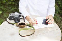 Moça com telefone celular, diário, xícara de café e a câmera velha Fotos de Stock