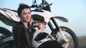 A moça com um capacete da motocicleta em suas mãos aprecia o por do sol perto de sua motocicleta video estoque