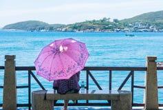 A moça com um guarda-chuva senta-se na margem e olha-se o mar Fotografia de Stock Royalty Free