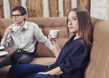 A moça com um indivíduo em um café senta-se no sofá com um copo nas mãos Fotos de Stock