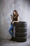 A moça com um telefone celular, está inclinando-se contra os pneus sobre Imagens de Stock