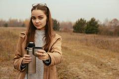 Moça com uma garrafa térmica em suas mãos imagem de stock royalty free