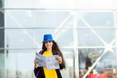 Moça com uma trouxa atrás de seu ombro que guarda um mapa, na rua perto do aeroporto fotografia de stock royalty free
