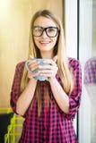 Moça com a xícara de café com bom humor na manhã no escritório moderno perto da janela Imagens de Stock Royalty Free