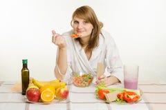 A moça come a salada vegetal do vegetariano com rolo de pão Foto de Stock