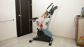 Moça contratada na bicicleta de exercício na sala vídeos de arquivo