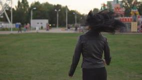 A moça corre e gerencie ao redor no fundo do parque ensolarado do verão video estoque