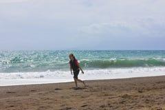 A moça corre e salta na praia perto do mar azul imagem de stock