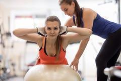 Moça de ajuda do instrutor da aptidão que faz exercícios traseiros no gym Fotos de Stock Royalty Free