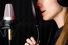 Moça de canto no estúdio de gravação foto de stock