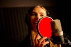 Moça de canto no estúdio de gravação Imagem de Stock