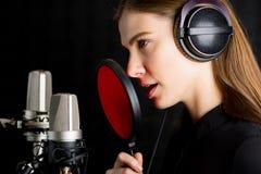 Moça de canto no estúdio de gravação Fotografia de Stock