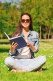 Moça de sorriso com o livro que senta-se no parque Foto de Stock Royalty Free