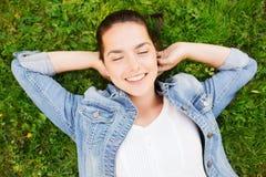 Moça de sorriso com os olhos fechados que encontram-se na grama Imagem de Stock Royalty Free