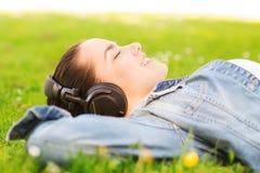 Moça de sorriso nos fones de ouvido que encontram-se na grama Foto de Stock