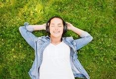 Moça de sorriso nos fones de ouvido que encontram-se na grama Imagem de Stock