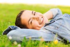 Moça de sorriso que encontra-se na grama Imagens de Stock Royalty Free