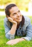 Moça de sorriso que encontra-se na grama Fotos de Stock