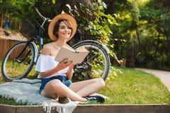 Moça de sorriso que lê um livro ao descansar imagem de stock royalty free