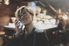Moça de sorriso que usa o smartphone na luz do bokeh do fulgor do fundo na cidade atmosférica da noite Menina do moderno que usa- fotos de stock