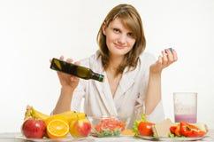 A moça derrama o óleo em uma salada vegetal da vitamina do vegetariano Foto de Stock Royalty Free