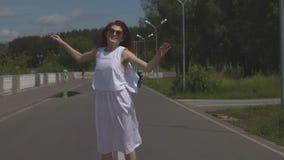 Moça despreocupada que salta e que tem o divertimento no parque do verão Menina atrativa nos óculos de sol e em um passeio branco filme