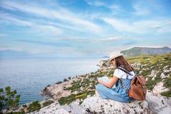 Moça do moderno com trouxa brilhante que aprecia o mar panorâmico da montanha, usando o mapa e olhando a distância imagem de stock