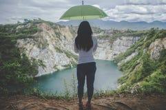 Moça do moderno com umbella verde que aprecia o por do sol no pico mo foto de stock royalty free
