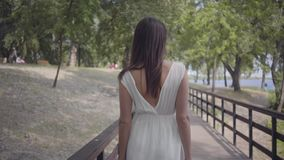 Moça do retrato com os óculos de sol vestindo do cabelo moreno e o vestido branco longo da forma do verão que anda ao longo do pa filme