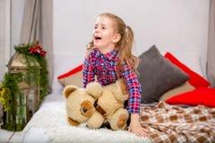 Moça doce feliz em um vestido azul-vermelho quadriculado que senta-se em uma cama com um urso e um riso de peluche imagens de stock